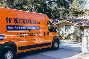 911 water damage restoration van parked outside of house