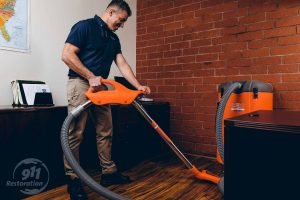 water damage restoration technician vacuums water in office